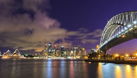 A view of Sydney Harbour at night time, with the iconic Harbour Bridge on the right, the Sydney skyline and the Sydney Opera House. Lights from the city are reflected in the harbour's calm water.