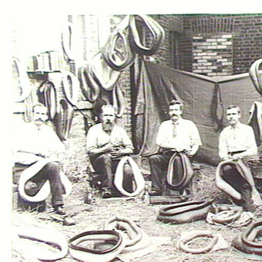 Men pack straw into horse collars at what is thought to be Holden and Frost, harness makers