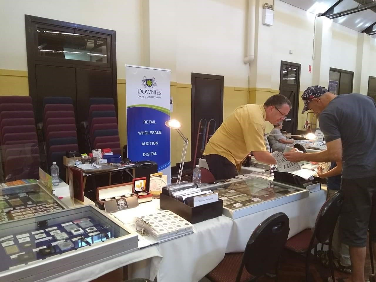 At the Numismatic Association of South Australia's Coin and Banknote Expo, Downies Numismatist Steve Kirby helps locate an ancient coin for a father and son who are collecting coins together